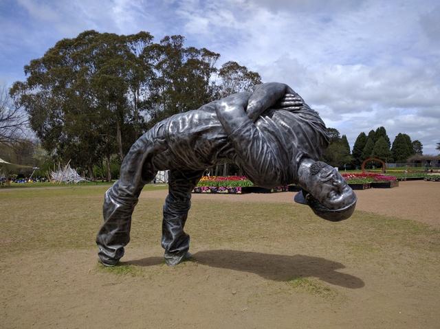 Sculpture of a man bending backwards.