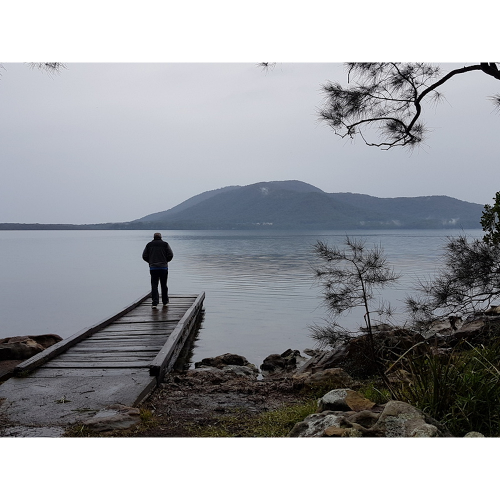Man standing on wooden jetty over a lake