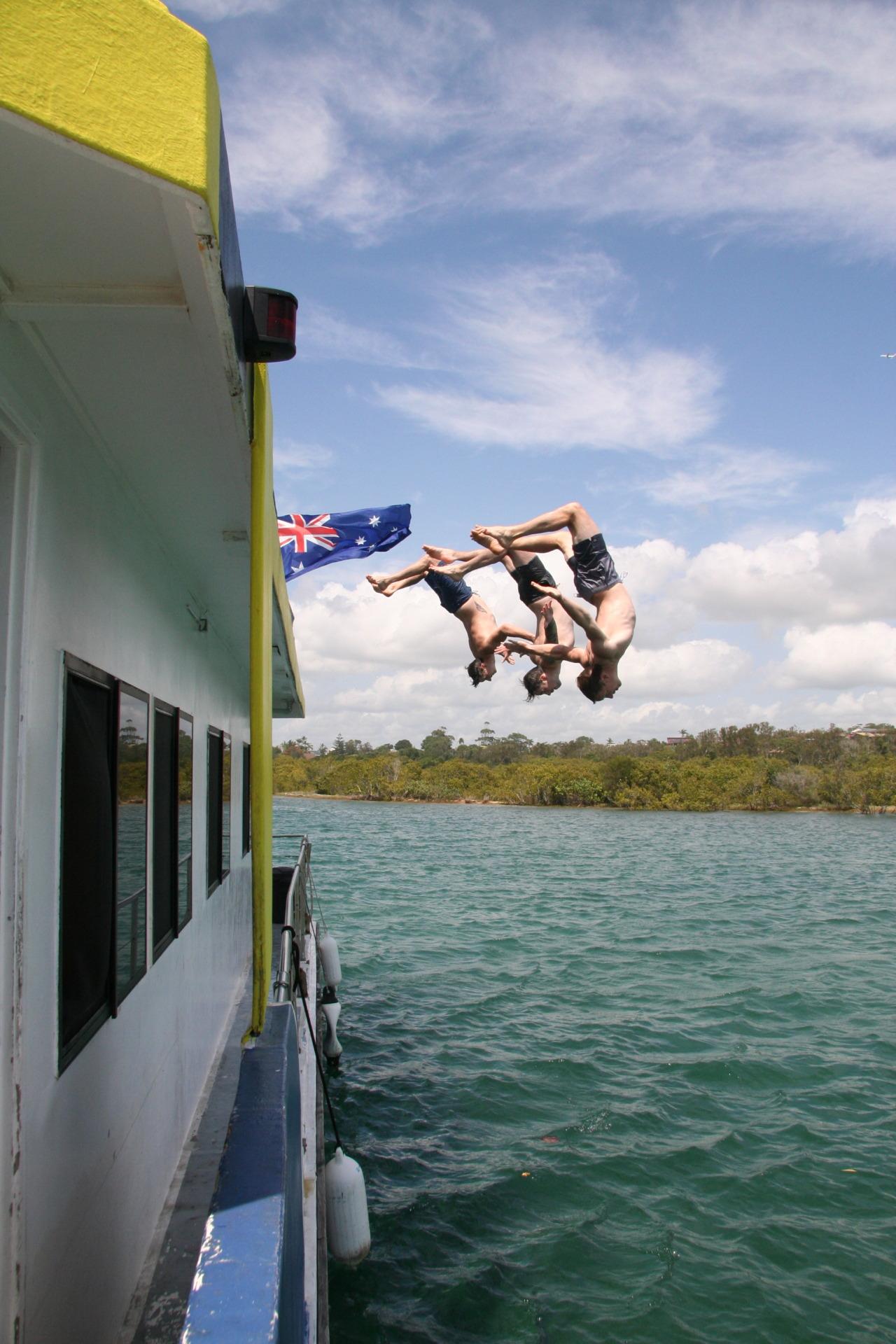 3 boys diving backwards off a boat